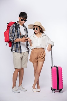 Man and woman dressed up wearing glasses to travel with suitcases