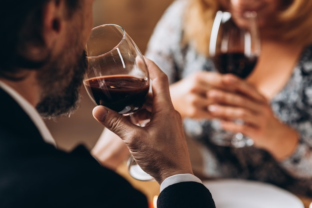 Man and woman drink red wine close up