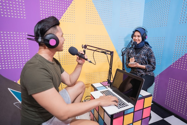 Man and woman during live interview in podcast studio together