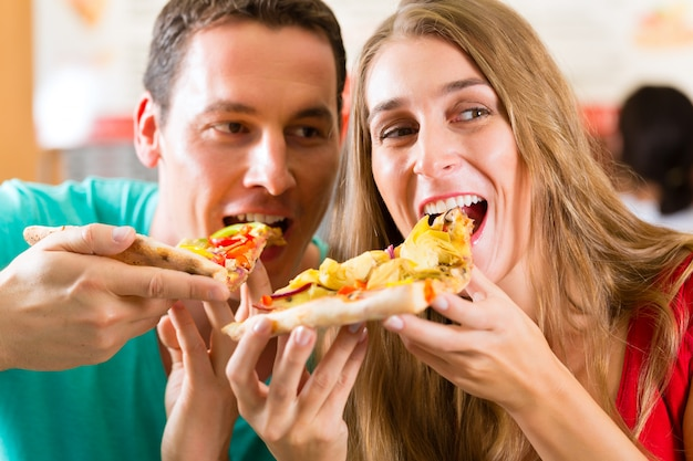 Man and woman eating a pizza