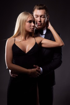Man and a woman in elegant outfits passionately embrace each other enjoying this moment
