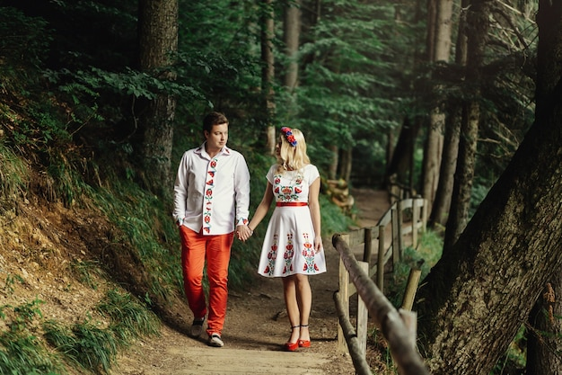 Man and woman in embroidered clothes walk along wooden path in the forest