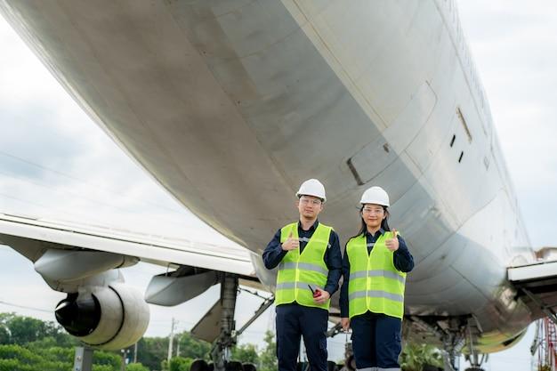 Man and woman engineer maintenance airplane thumb up