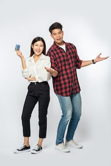 Man and woman enjoy using credit cards for shopping