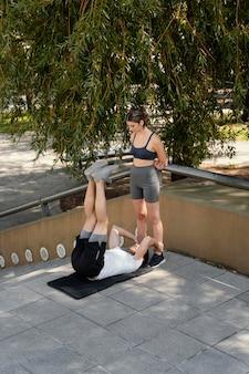 Uomo e donna che esercitano insieme all'aperto