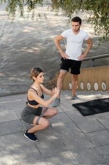 Uomo e donna che esercitano insieme fuori