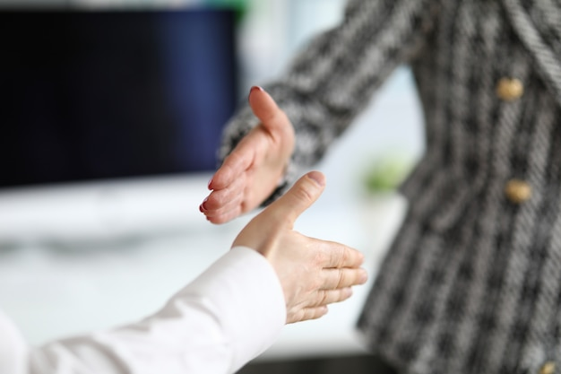 Man and woman extend their hands in greeting