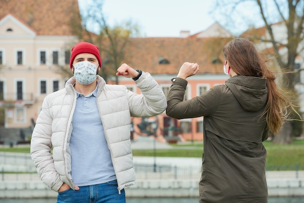 A man and a woman in face masks bump elbows instead of greeting with a hug.