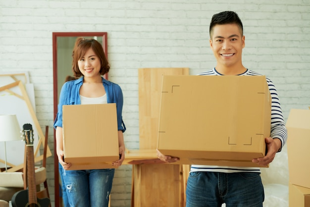 Man and woman facing camera holding cardboard boxes