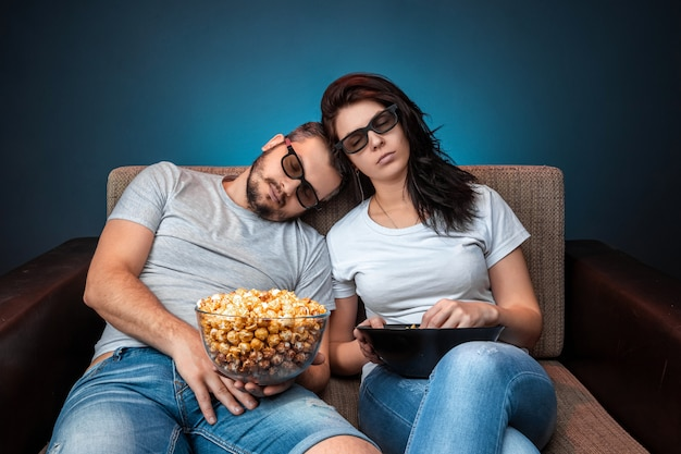 A man and a woman, a family watching a movie or a series in 3d glasses, a blue wall. the concept of a cinema, films, emotions, surprise, leisure, streaming platforms.