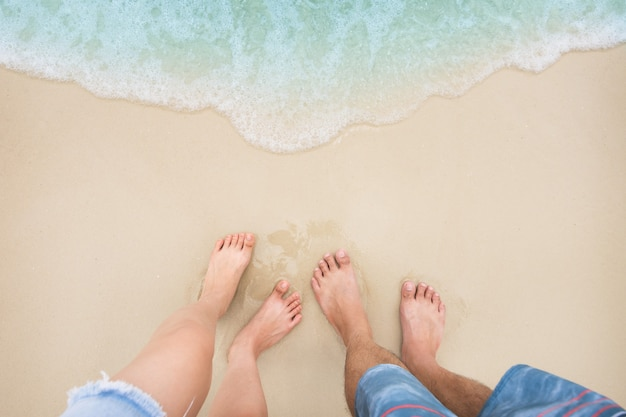 Man and woman feet are standing on the sandy beach with soft ocean wave.