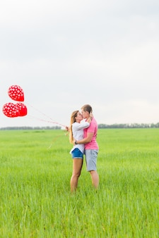 Man and woman on the field with red balloons. happy couple on nature.