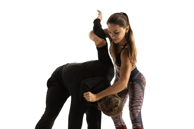 Man and woman fighting on white, women's self-defense concept