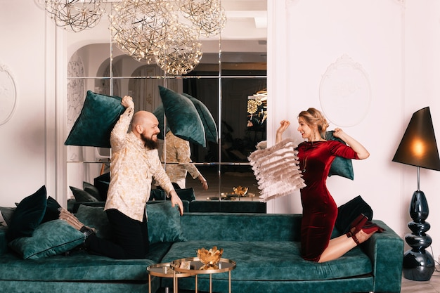 Man and woman fighting with pillows. comic pillow fight. the couple in love arranged a fight with pillows on the bed.