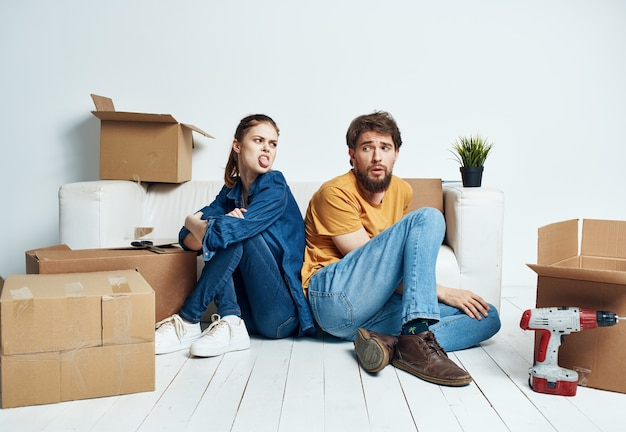 Man and woman on the floor with boxes planning moving to apartment