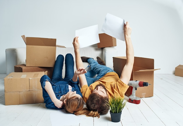 Man and woman on the floor with boxes planning moving