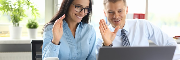 Man and woman greet interlocutor with hand on online call on laptop