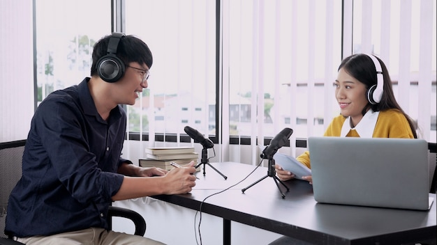 Man and woman guest recording podcast or interview each other for radio in studio together.
