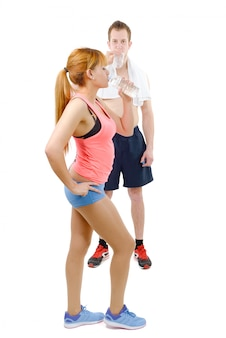 Man and woman at gym in fitness attire holding water bottles