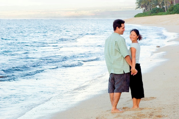 Man and woman hand in hand on beach