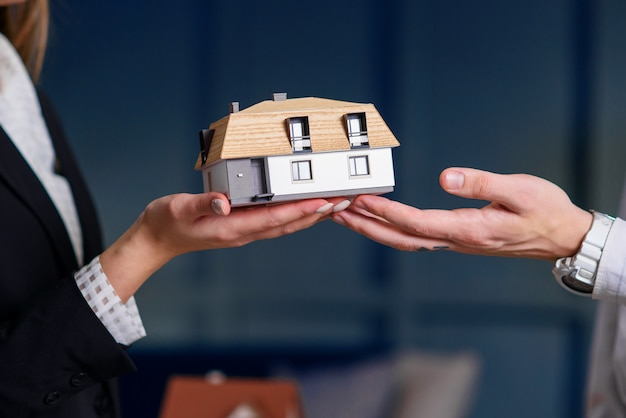 Man and woman hands holding 3d model of house.