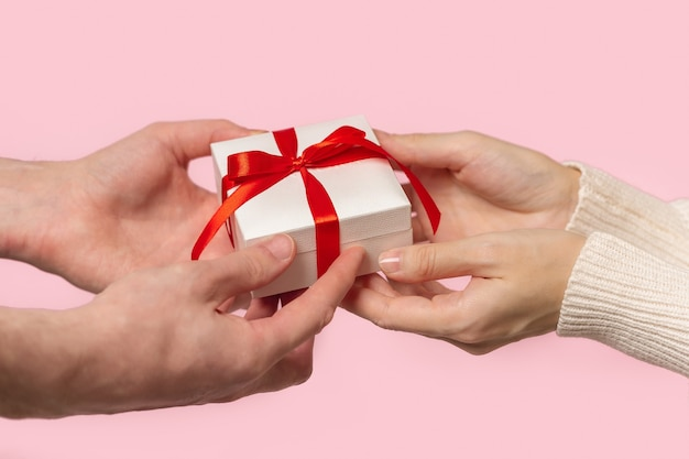 Man and woman hands holding gift box with red bow on pink