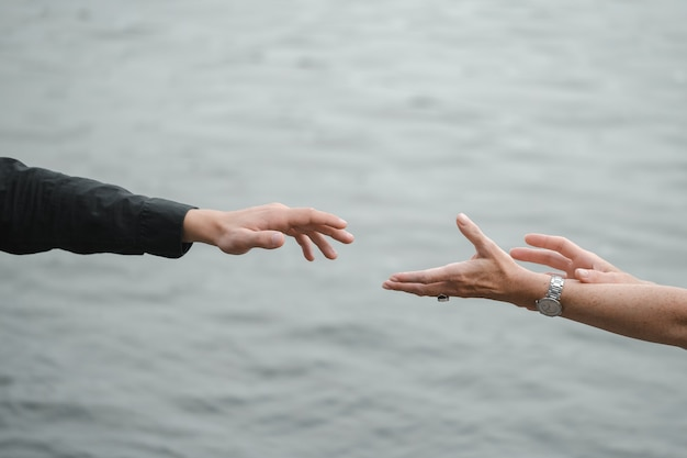 Man and woman hands reaching out holding near water