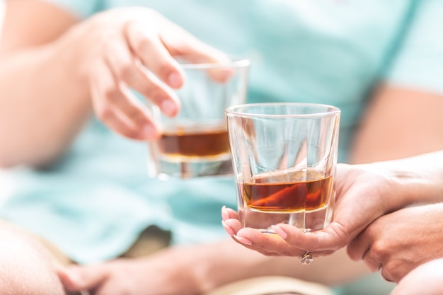 Man and woman hands toasting with glasses of whiskey brandy or rum indoors - closeup.