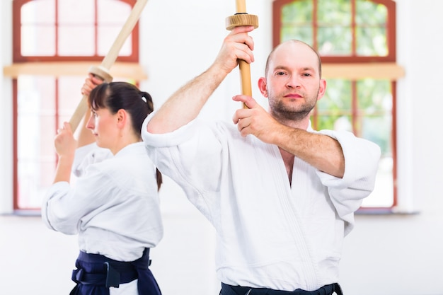 Man and woman having aikido sword fight