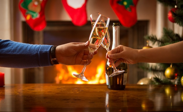 Man and woman having christmas dinner and clinking glasses next to burning fireplace