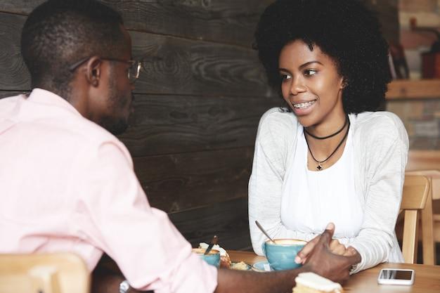 Uomo e donna che hanno caffè nella caffetteria