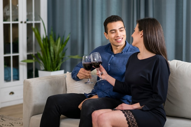 Man and woman having a glass of wine while sitting on the couch