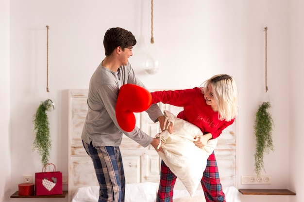 Man and woman having a pillow fight in the bedroom