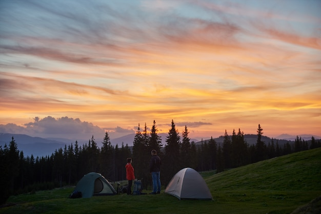 Man and woman having a rest in the camping near two tents in the mountains while hiking together with their backpacks enjoying beautiful sunset