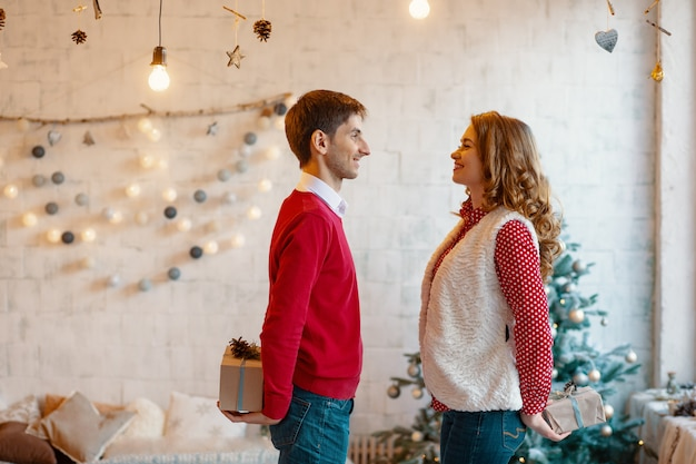 Man and woman hiding christmas present boxes behind back