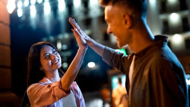 Man and woman high-fiving at night in the city lights