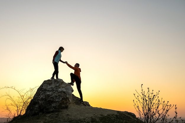 Man and woman hikers helping each other to climb a big stone at sunset in mountains. couple climbing on a high rock in evening nature. tourism, traveling and healthy lifestyle concept.