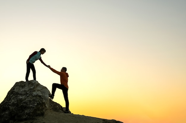 Man and woman hikers helping each other to climb a big stone at sunset in mountains