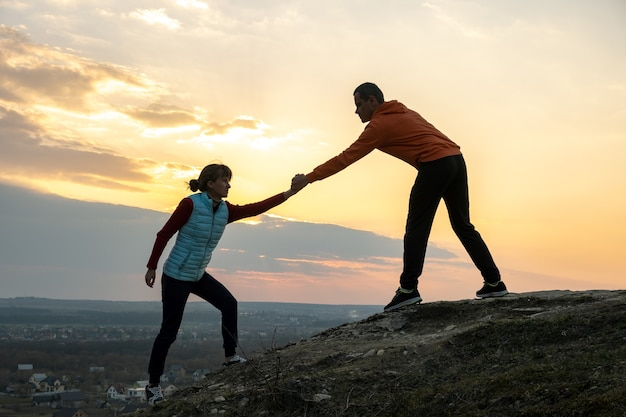 Man and woman hikers helping each other to climb stone at sunset in mountains.