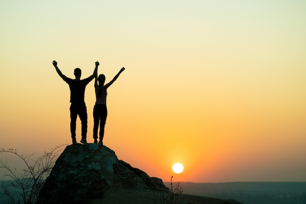 Man and woman hikers standing on a big stone at sunset in mountains. couple raising up hands on high rock in evening nature. tourism, traveling and healthy lifestyle concept.