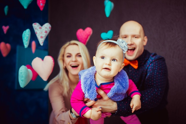 Man and woman hold their little daughter like an airplane standing in black room with hearts around them
