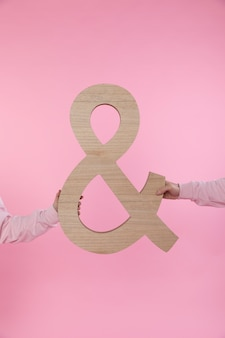 Man and woman holding big symbol of ampersand