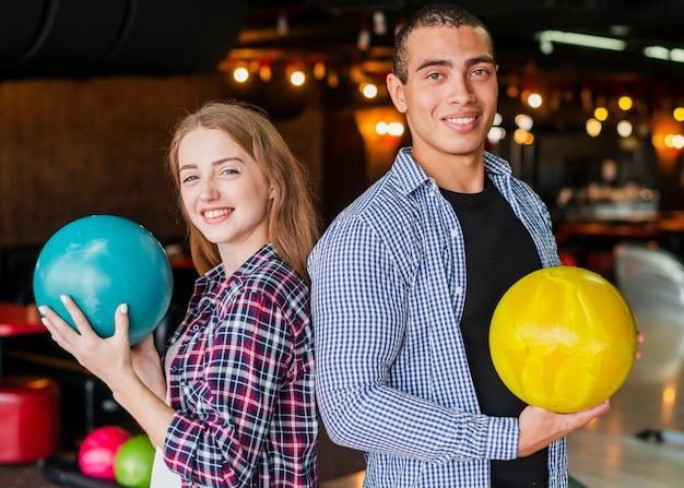 Uomo e donna che tengono le palle da bowling