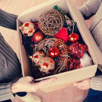 Man and woman holding a cardboard box with toys for christmas tree ornaments