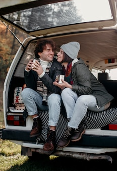 Man and woman holding cups of coffee in a van