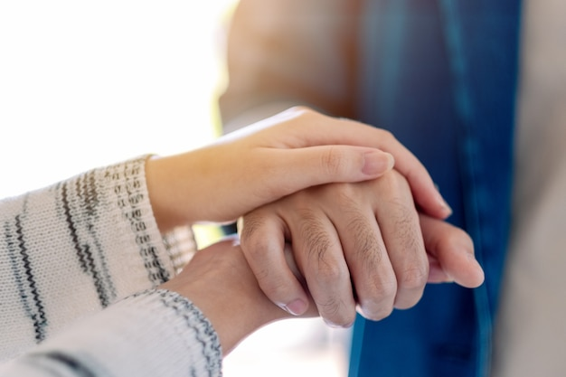 A man and a woman holding each other hands for comfort and sympathy