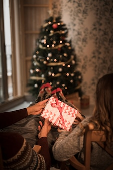 Man and woman holding gift box on chairs near christmas tree