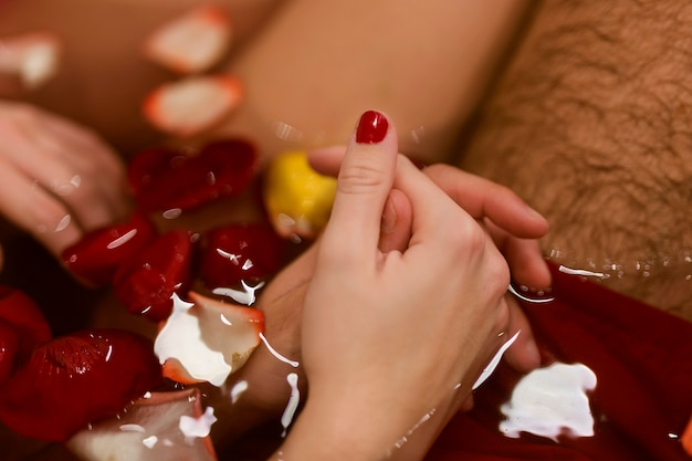 Man and woman holding hands in the bathtub close-up
