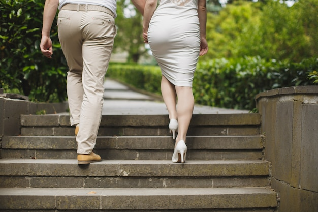 Man and woman holding hands and going up the stairs