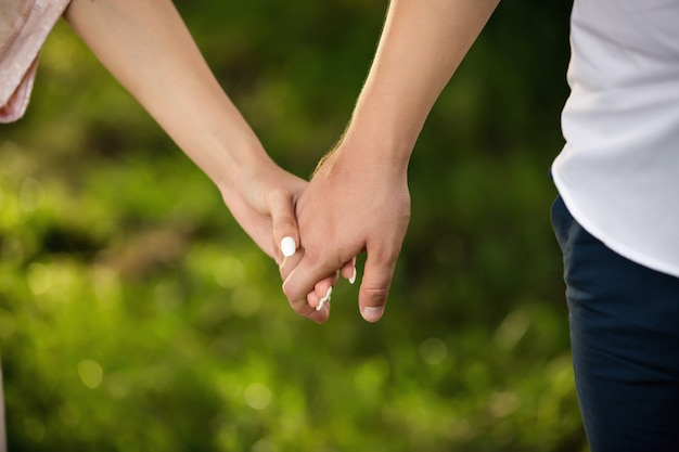 Man and woman holding hands on green background. heterosexual couple in love.